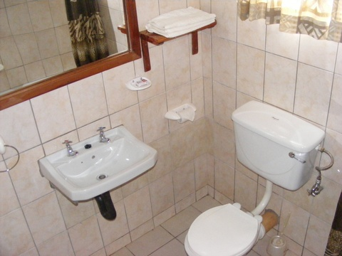 Double room toilet and handbasin with mirror and toiletries shelf